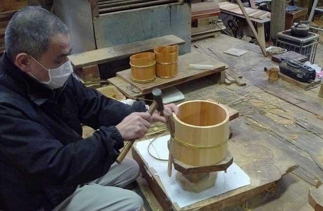 竹の箍を木桶を締め込むように取り付ける