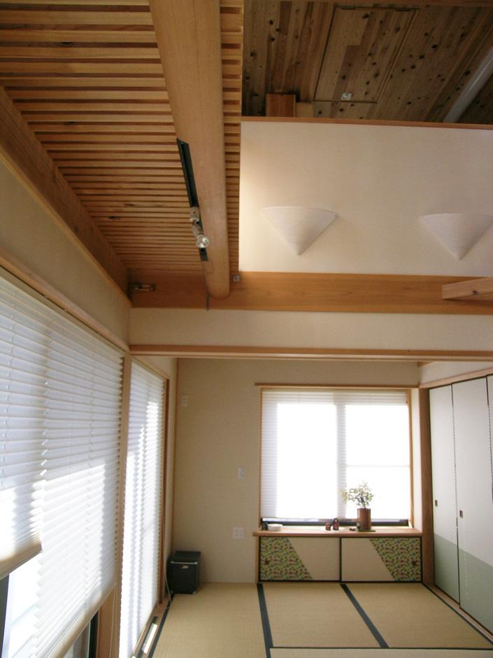 居間から和室と吹吹抜上部を望む写真。左上に見えるのは吉野杉の丸太梁・太鼓落としにスノコ状の歩行床を見上げたところ。